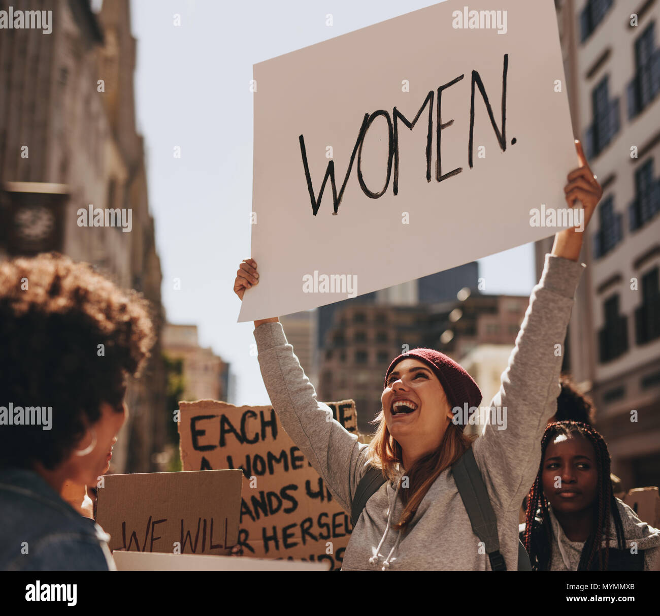 Happy young woman hand written protest sign at women's march. Group of females demonstrating outdoors. Stock Photo