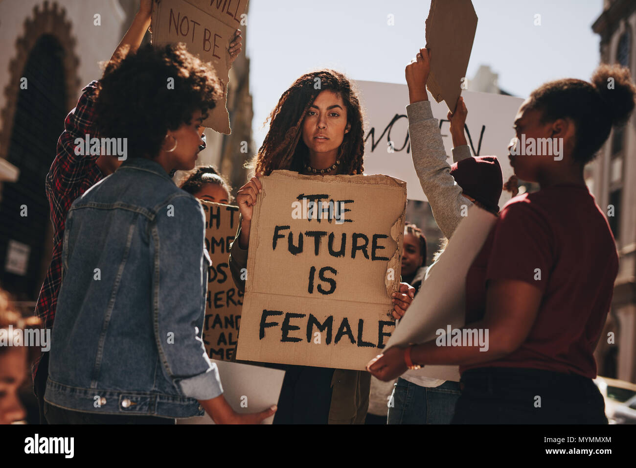 Women protesters hold up signs of the future is female. Group of women protesting outdoors for female empowerment. - Stock Image