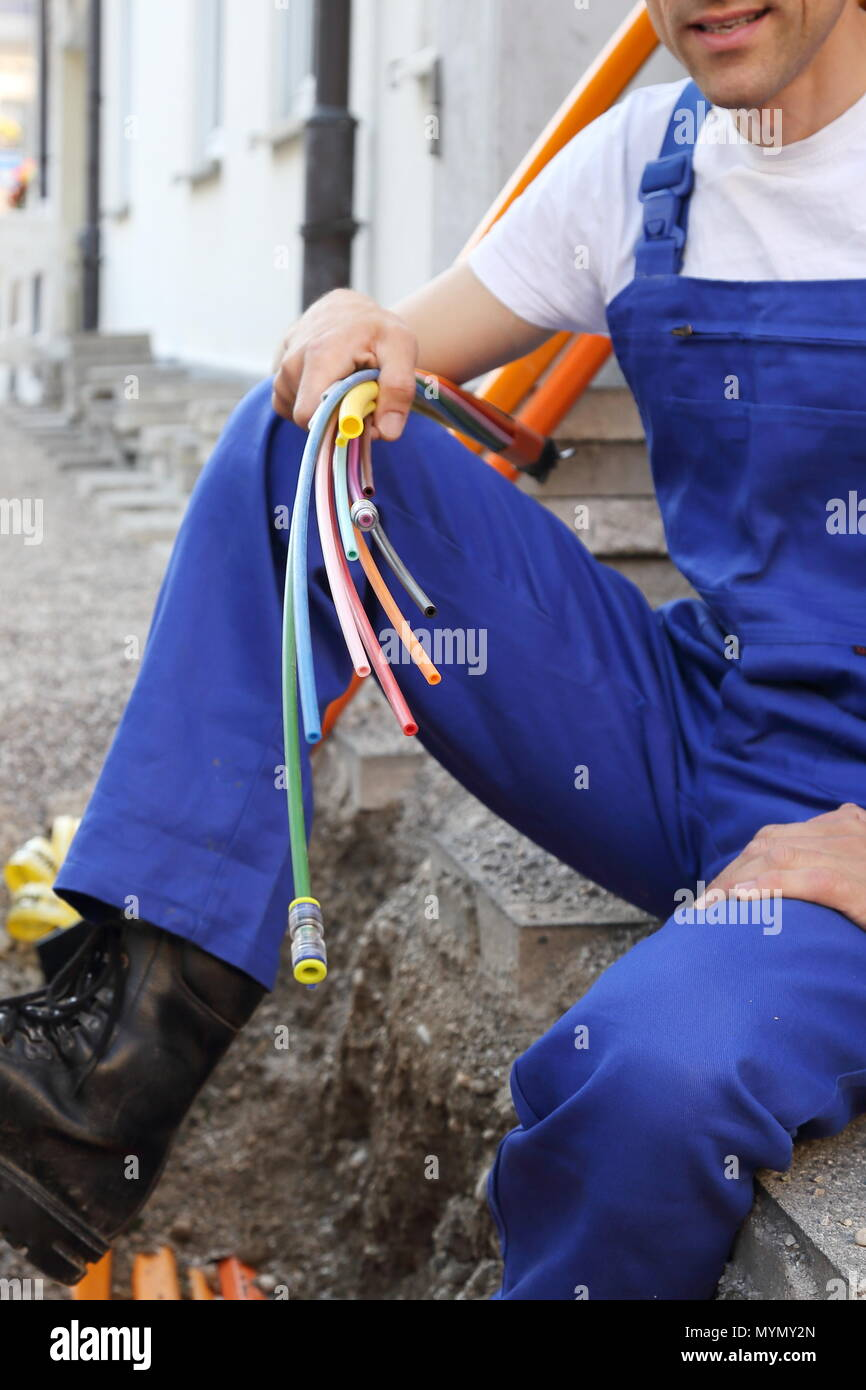 A Fiber optic broadband cable with worker - Stock Image