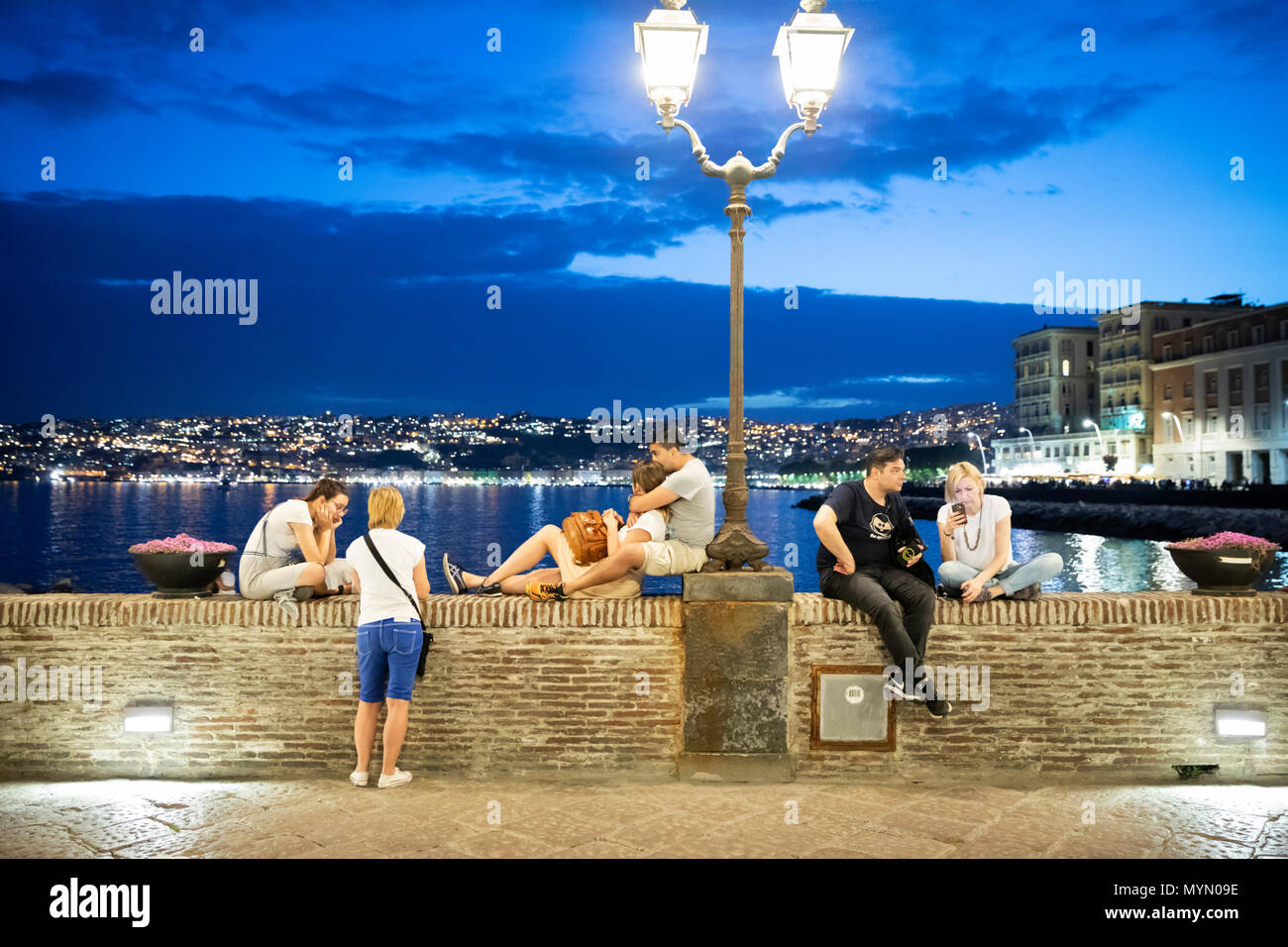 People sitting on wall under street lamp by the Castel dell Ovo at dusk, Naples, Campania, Italy, Europe - Stock Image