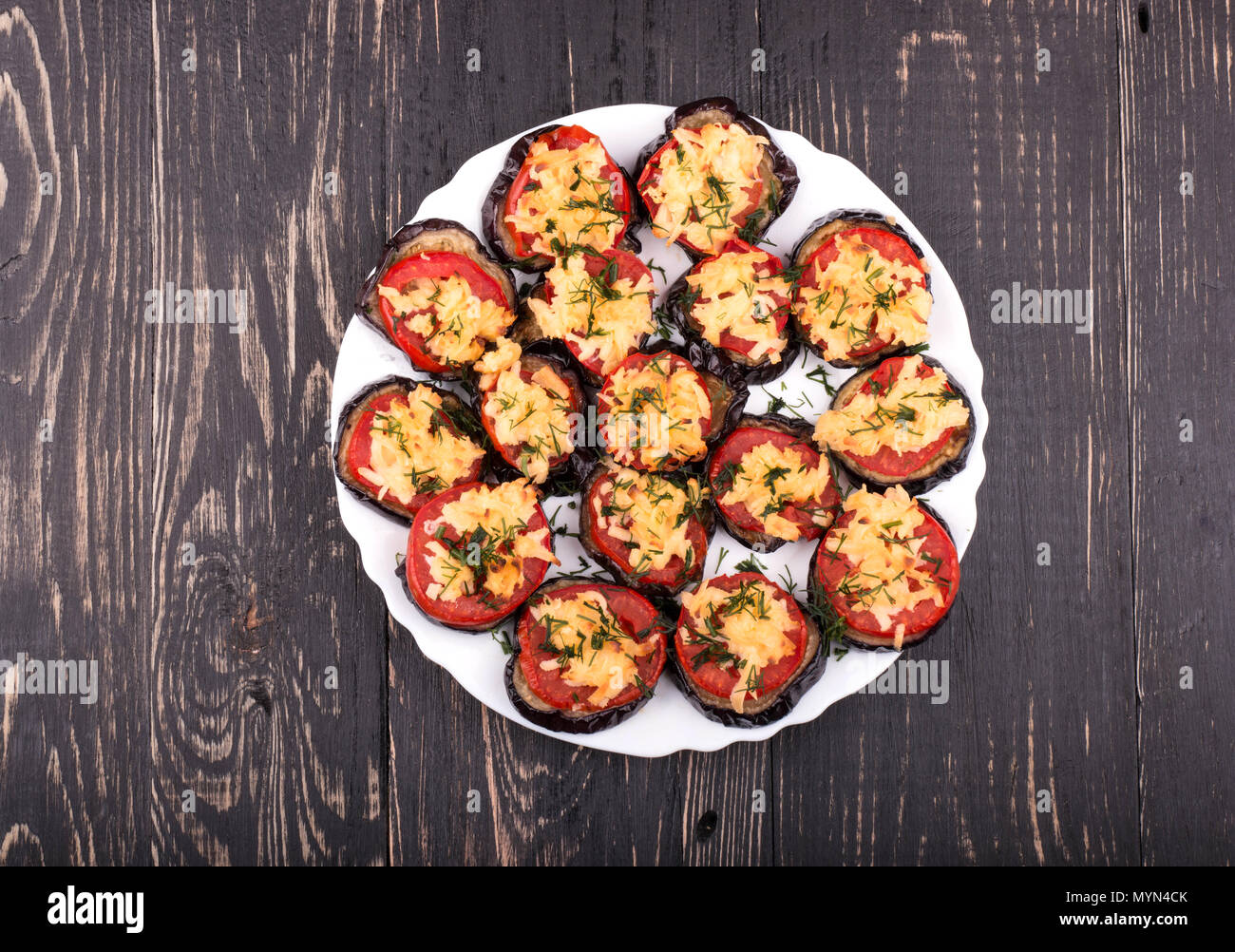 Dish of fried slices of eggplant, tomatoes and sprinkle with cheese and dill in a bowl on a wooden background Stock Photo
