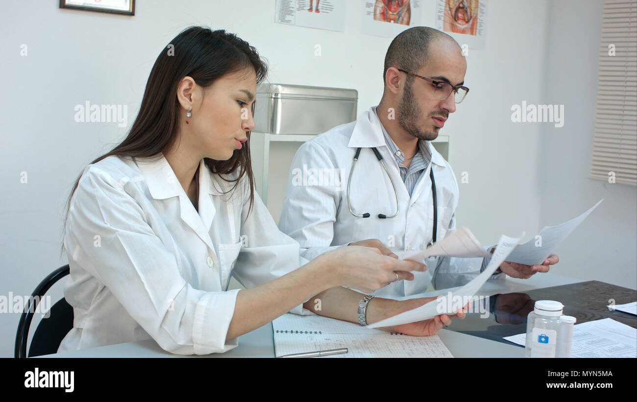 Two busy doctors working with papers and xray images