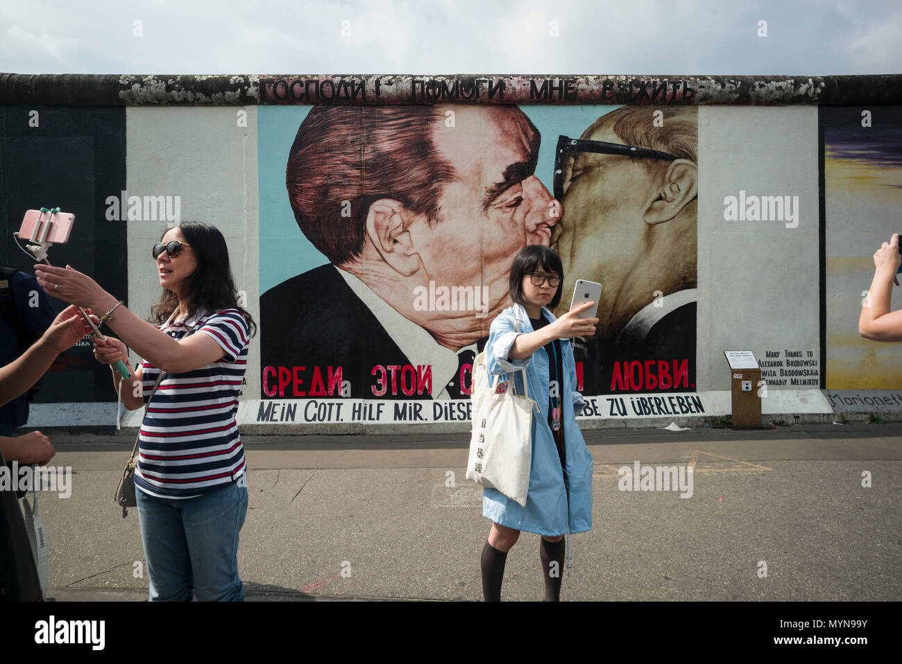 Berlin. Germany. Tourists pose for photos infront of one of the remaining sections of the Berlin Wall at the East Side Gallery.   Tourists pose for ph - Stock Image