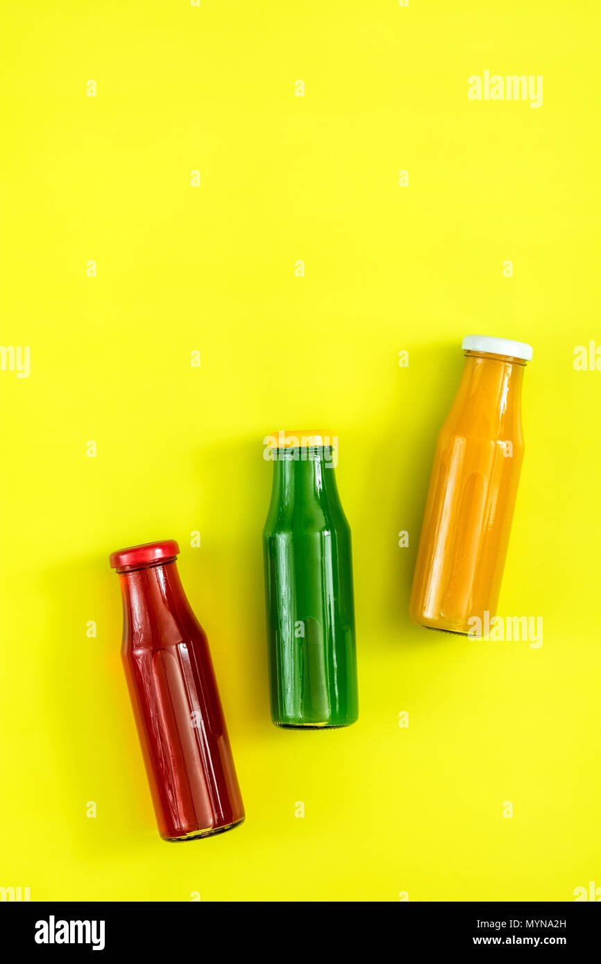 Beautiful food art background. Yellow, red and green juices in glass bottles on bright green surface. - Stock Image