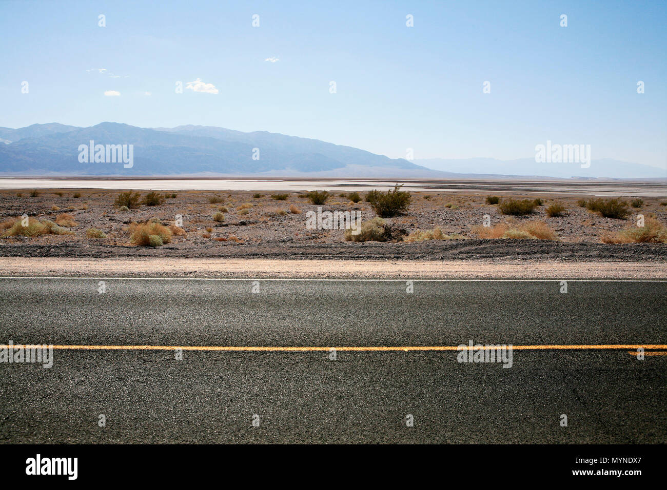 Tarmac highway with bright yellow road markings in California desert on hot sunny day - Stock Image