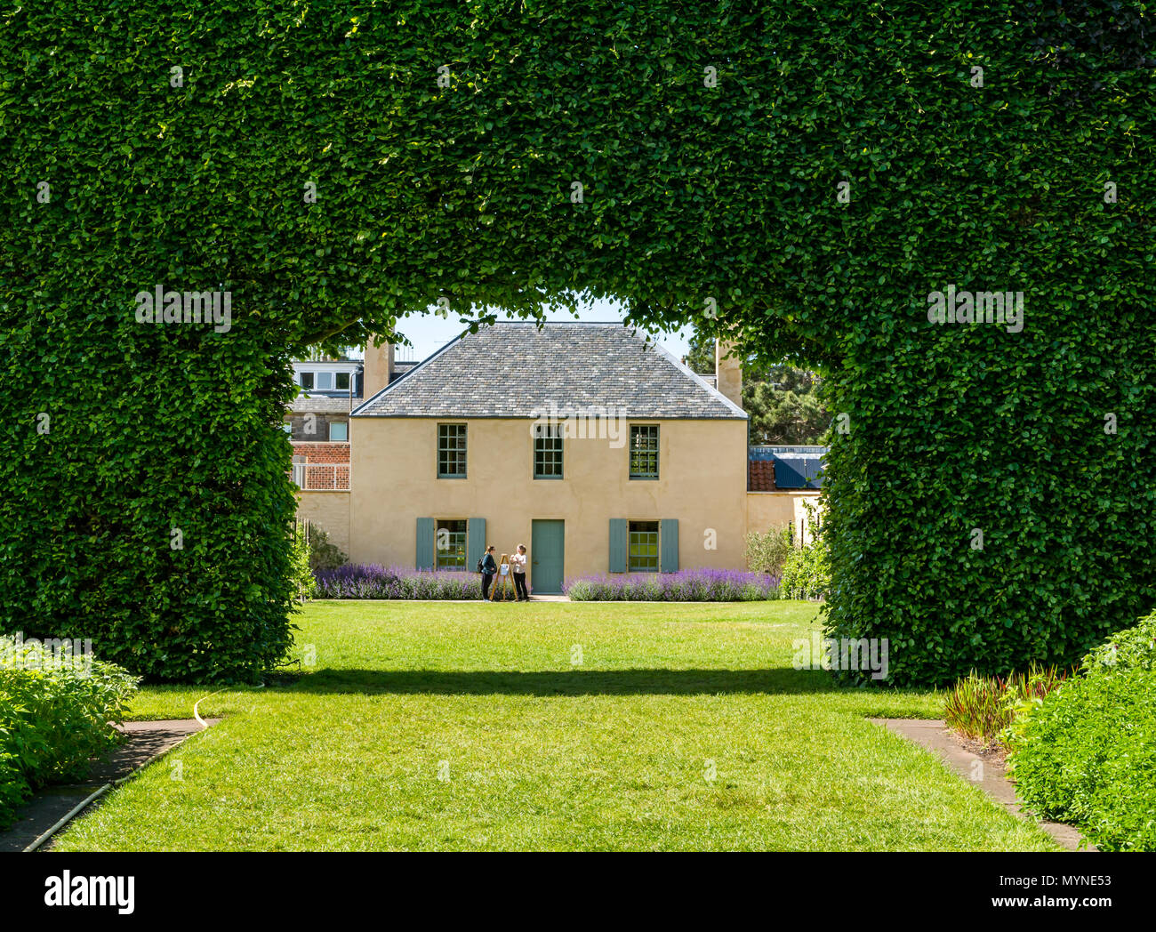 Botanic Cottage through giant beech hedge, moved from Leith Walk original site with two women chatting, Royal Botanic garden, Edinburgh, Scotland, UK - Stock Image