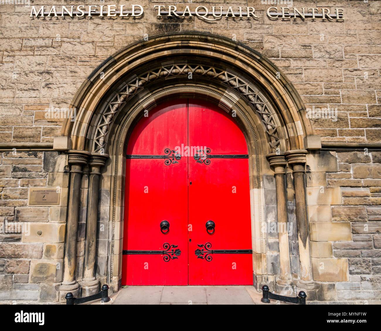 Bright red ornate arched door with elaborate hinges, Mansfield Traquair Centre, SCVO headquarters, Edinburgh, Scotland, UK - Stock Image