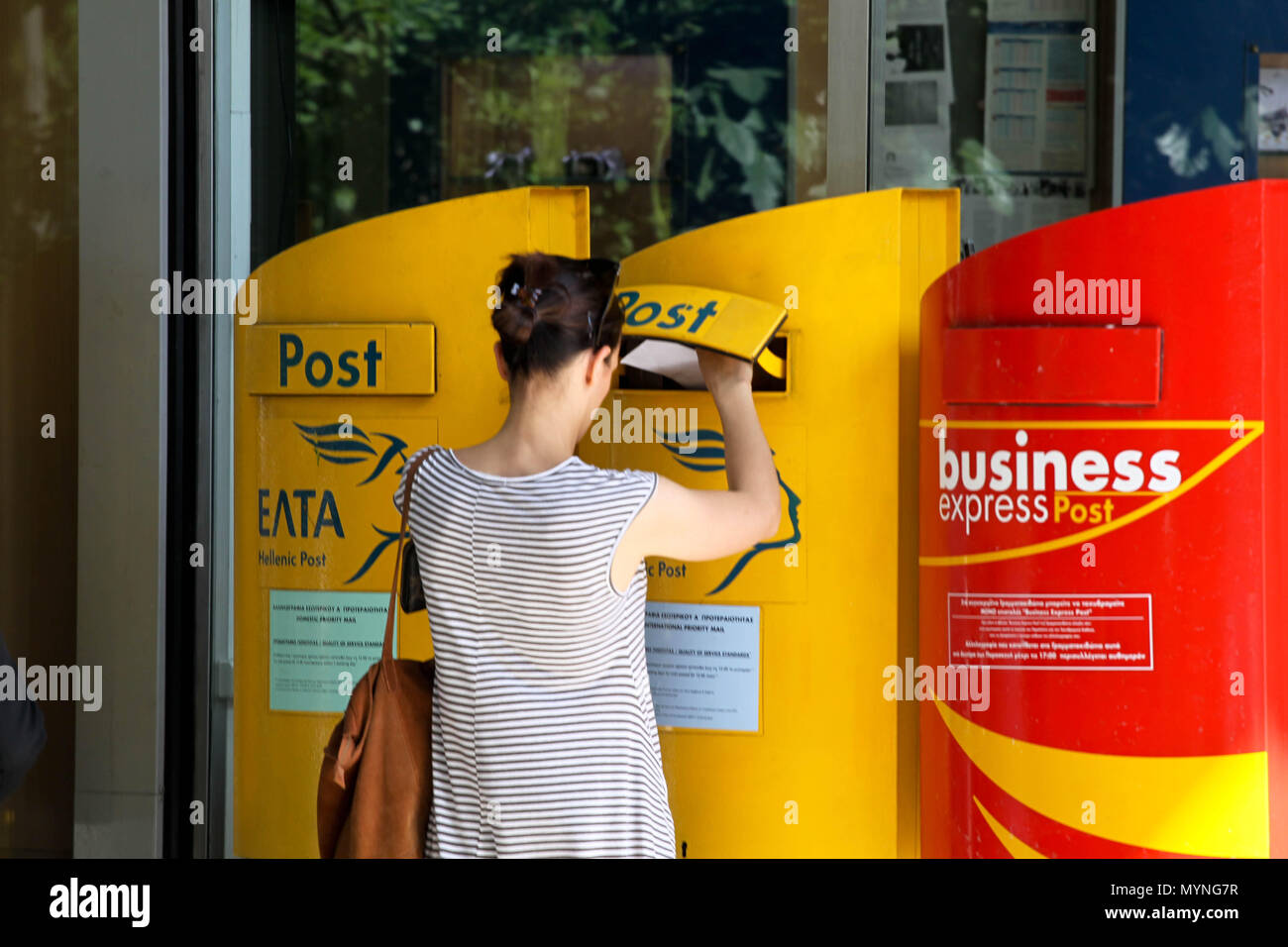 Woman posting a letter outside a Post office in Athens Greece - Stock Image
