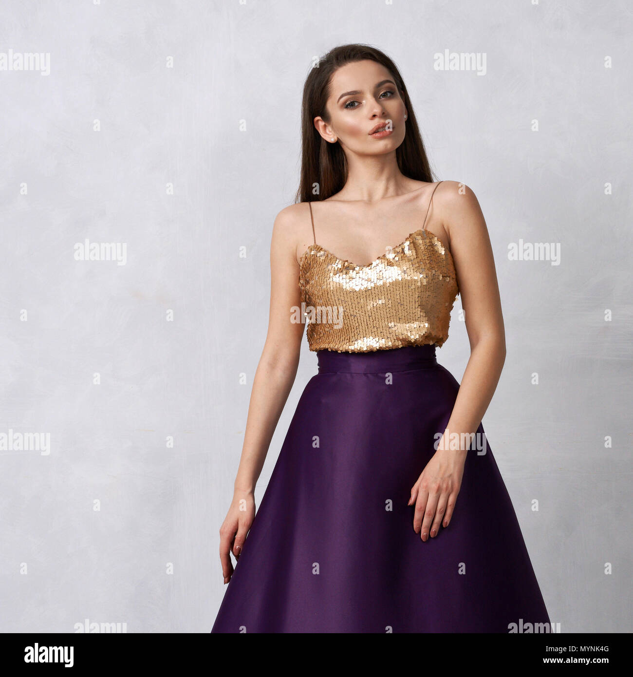 b380f798a334a Young woman in formal dress with golden sequin top and purple sa ...