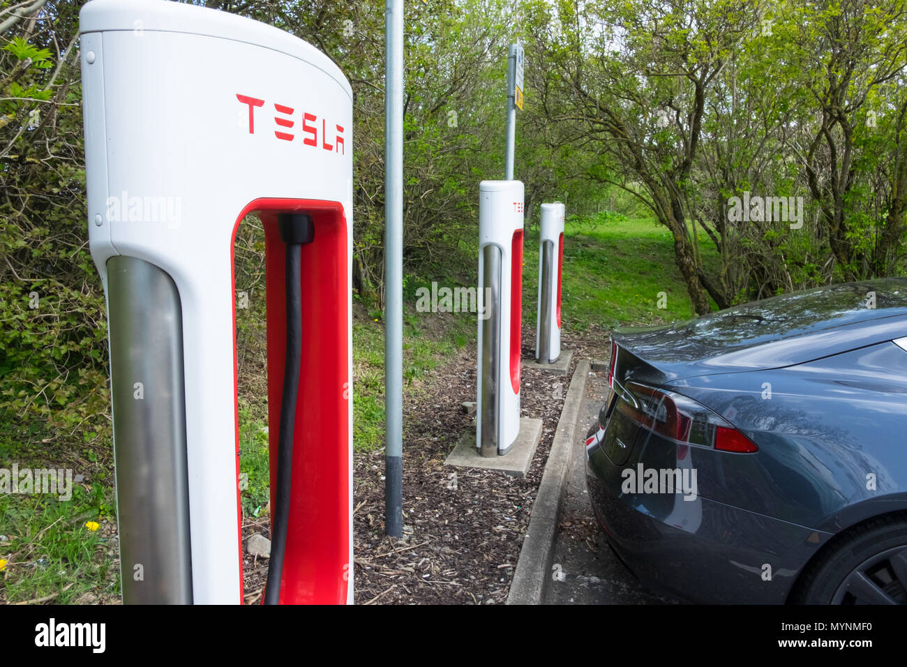 Tesla car next to supercharger at service area in UK - Stock Image