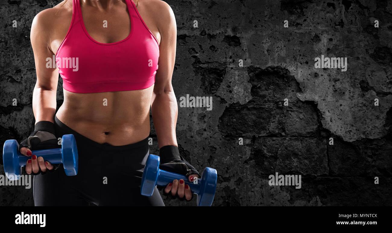 Athletic woman training biceps on grunge background - Stock Image