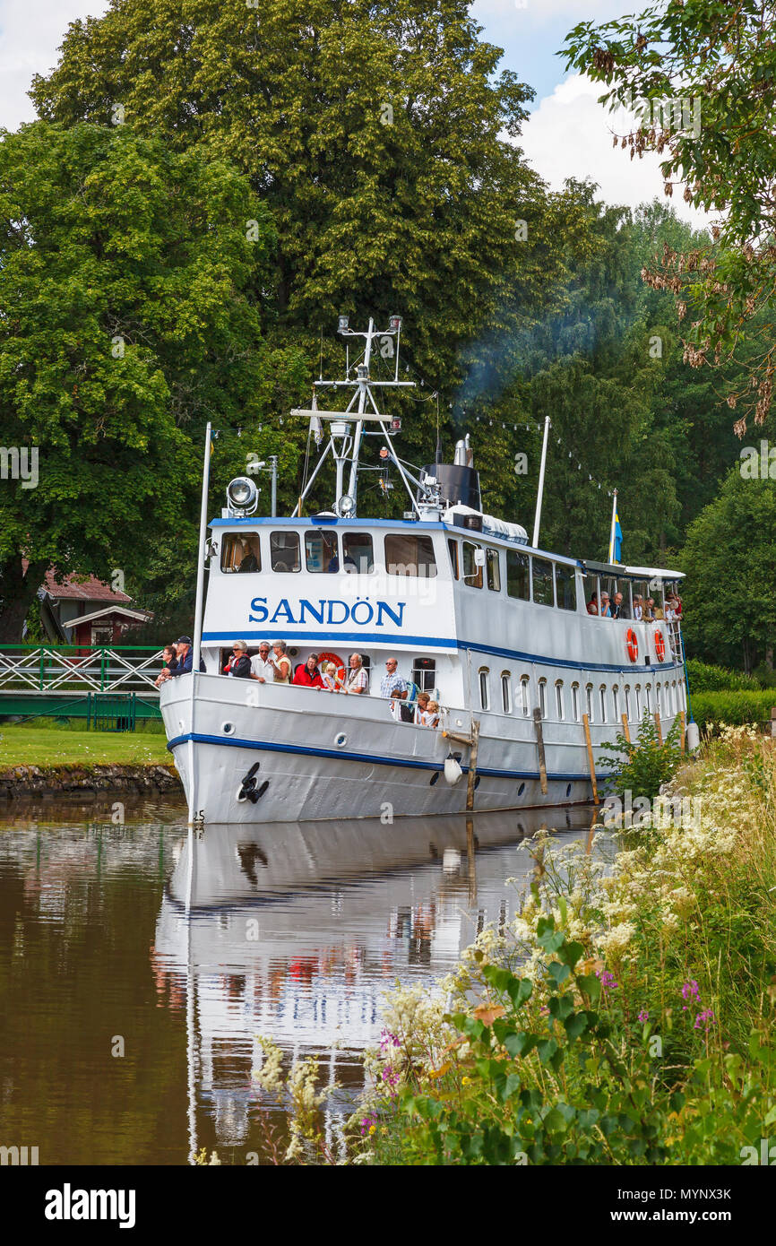 Passenger ship with tourists on a canal in an idyllic Swedish summer landscape - Stock Image