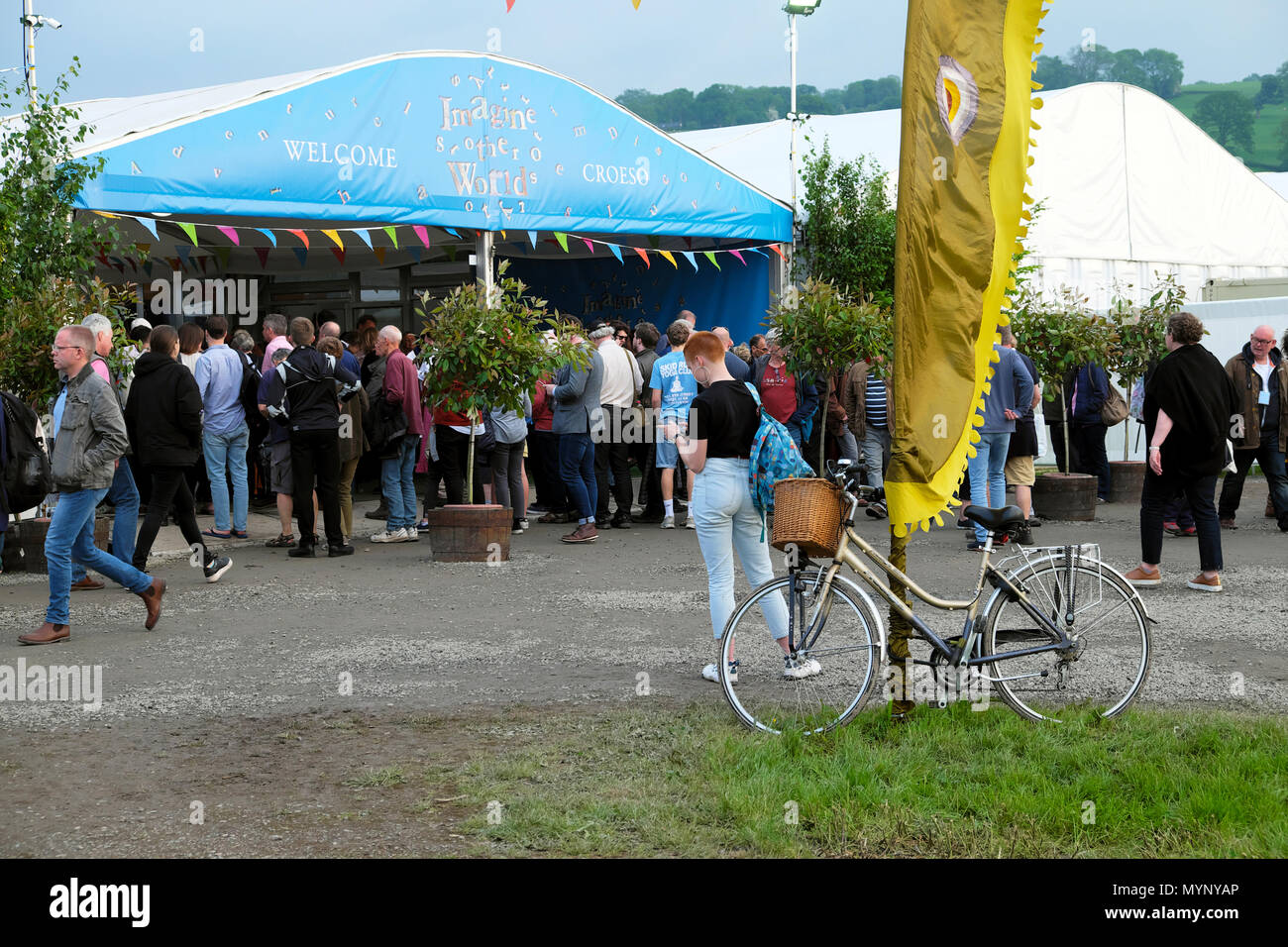 Hay Festival entrance with bicycle, banner and visitors outside, woman looking at programme Saturday evening 26 May 2018 Hay-on-Wye UK  KATHY DEWITT Stock Photo