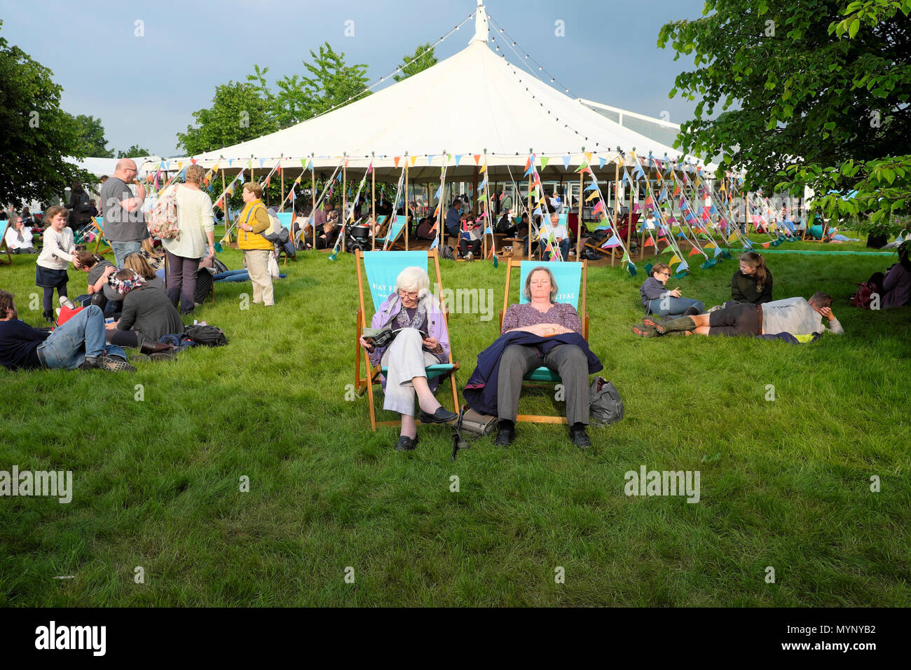 People in deckchairs and visitors relaxing at the marquee on the Hay Book Festival site May 2018 in Hay-on-Wye Wales UK  KATHY DEWITT - Stock Image