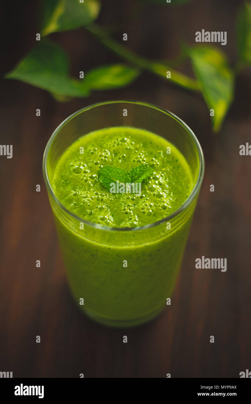 Healthy smoothie with fruits and veggies on a table with plant Stock Photo