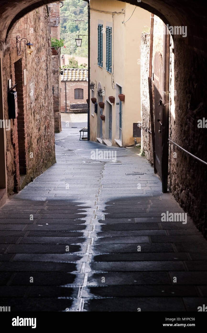 medieval narrow sreet in asciano, Italy - Stock Image