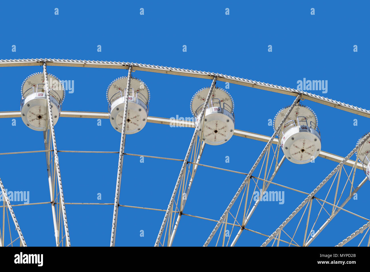 Ferris wheel with white cabins for the passengers, seen from below, at a fairground - Stock Image
