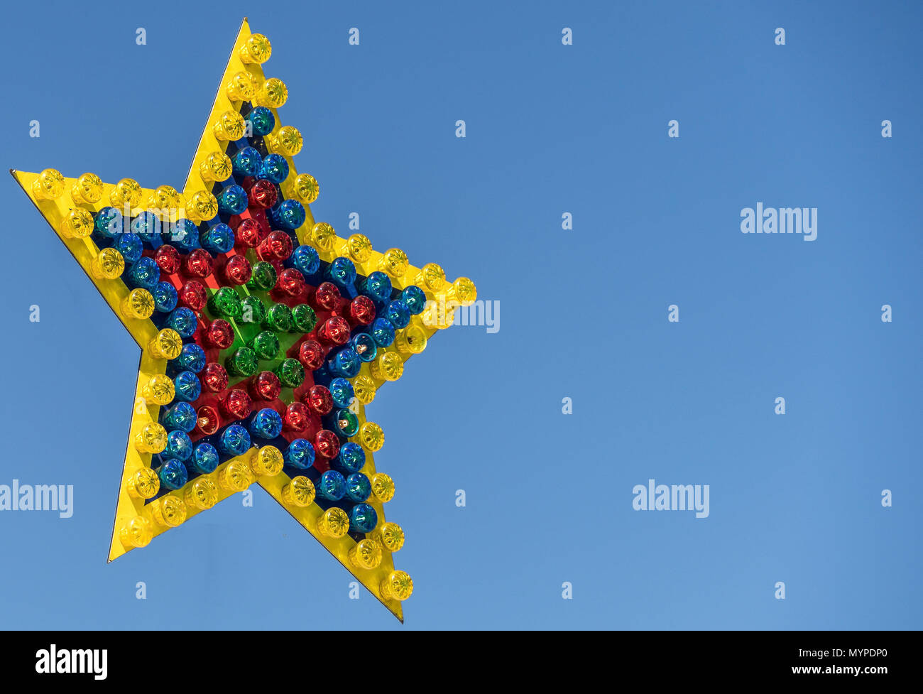 Colorful shining star from many single lamps with different colors on a fair, exempted before a blue sky, isolated - Stock Image