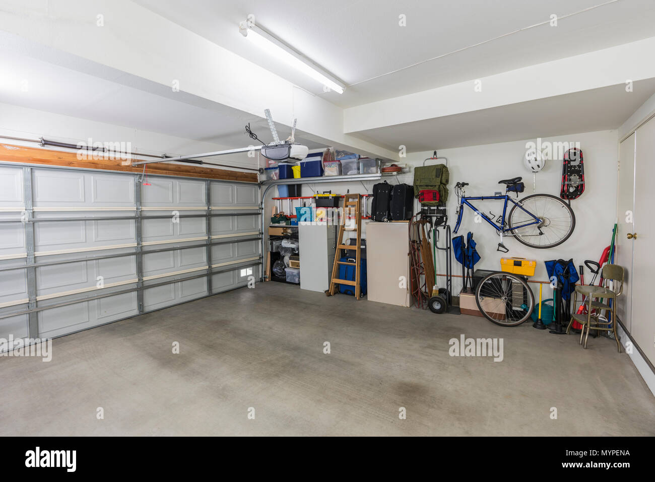 Clean suburban two car garage interior with tools, file cabinets and sports equipment. - Stock Image