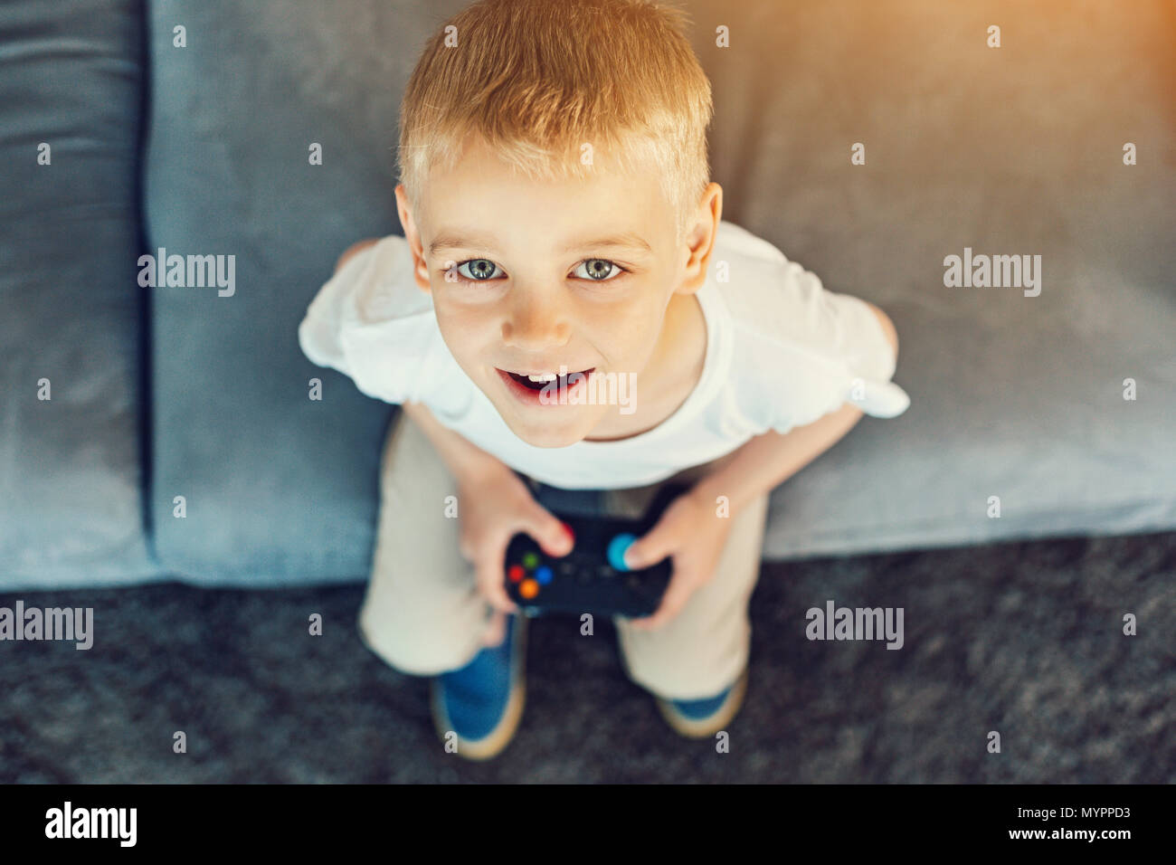 Playful boy sitting with a games console - Stock Image