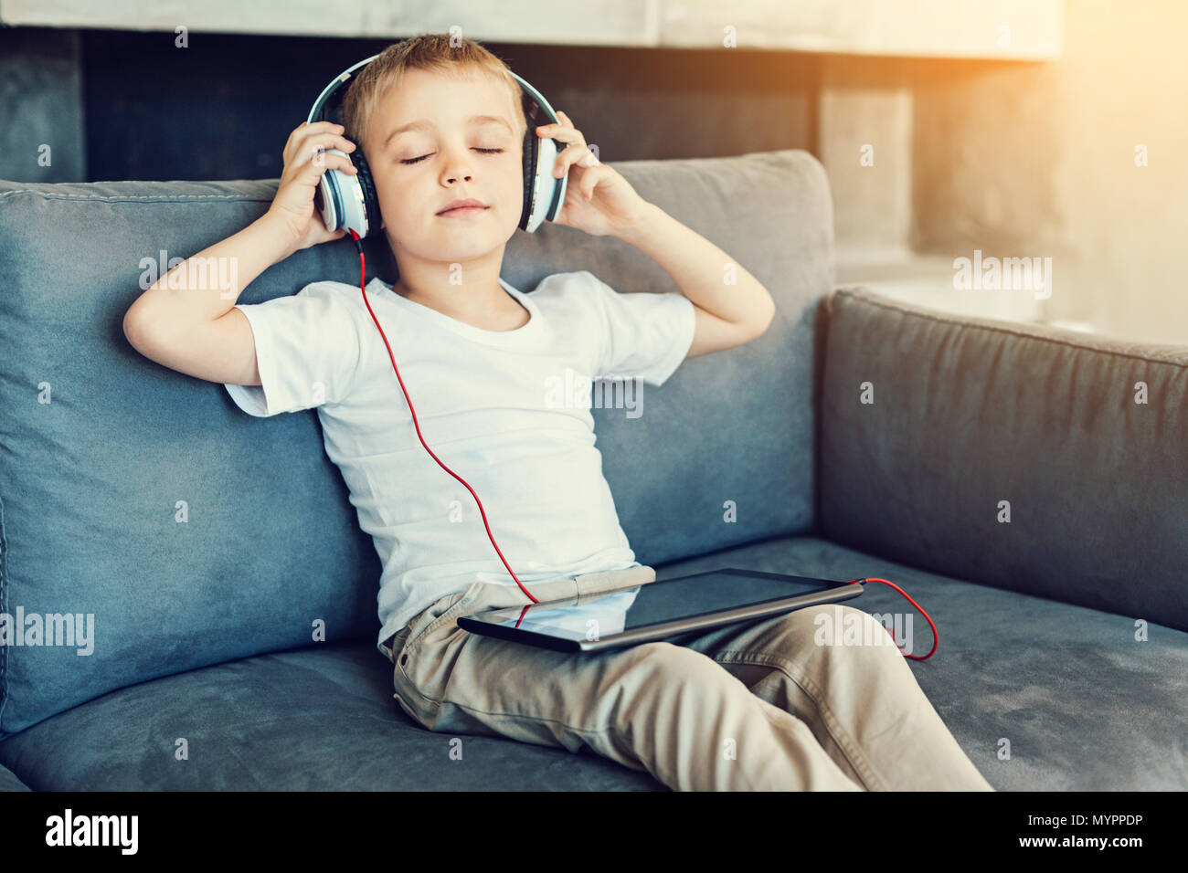 Relaxing boy sitting with his eyes closed - Stock Image