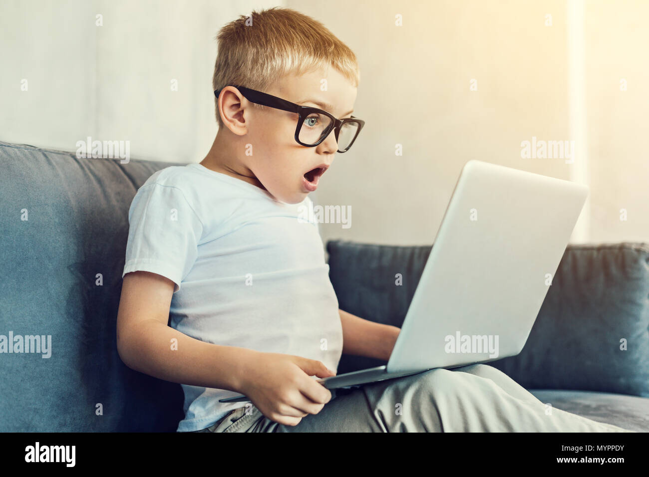Astonished boy in glasses holding a laptop - Stock Image