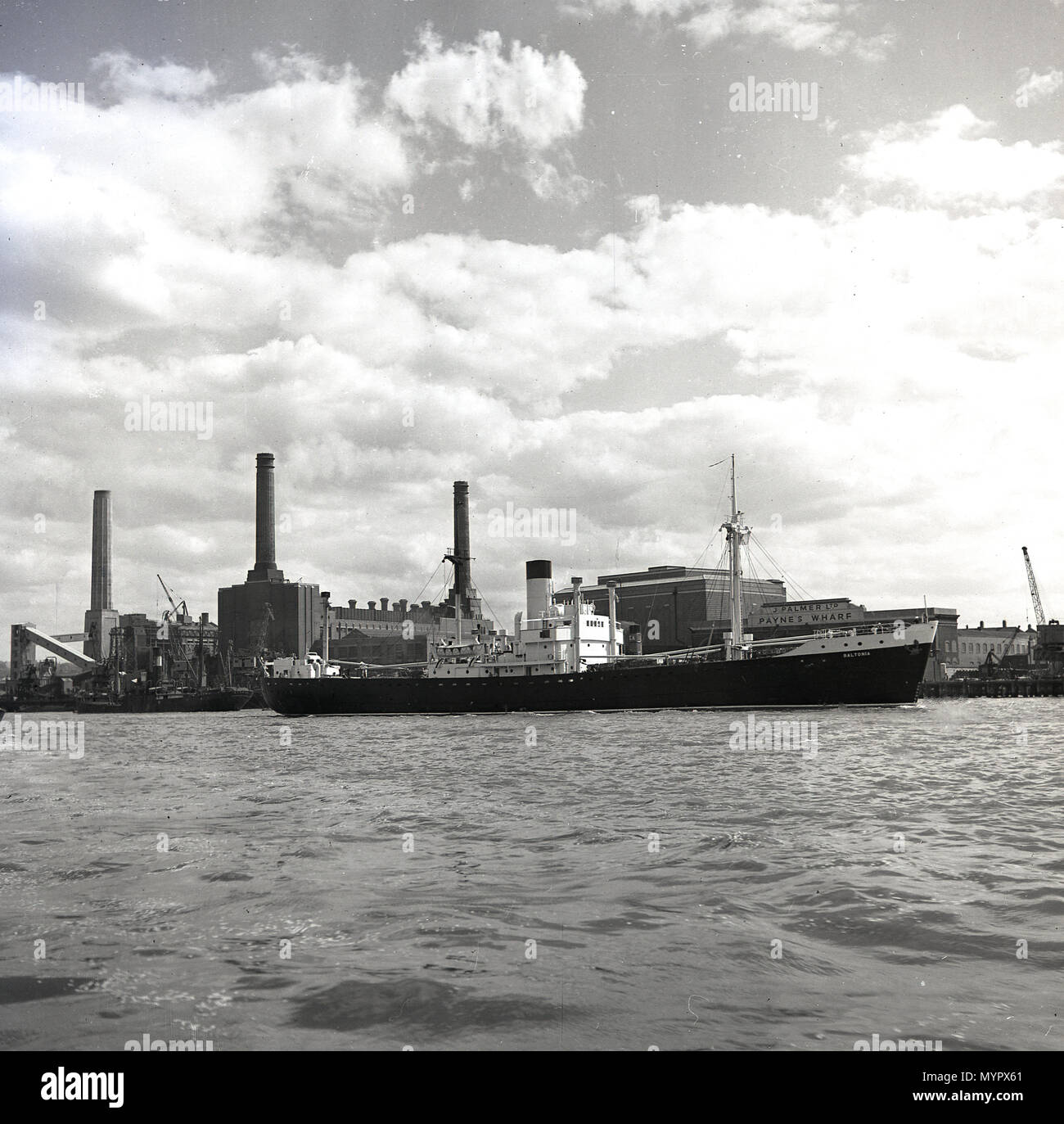 Early 1950s, view from across the river Thames to the south of the river and a working Battersea power station, which at this time, only had three chimneys, London, England, UK. The fourth chimney stack, the south east one, was erected in 1955. - Stock Image