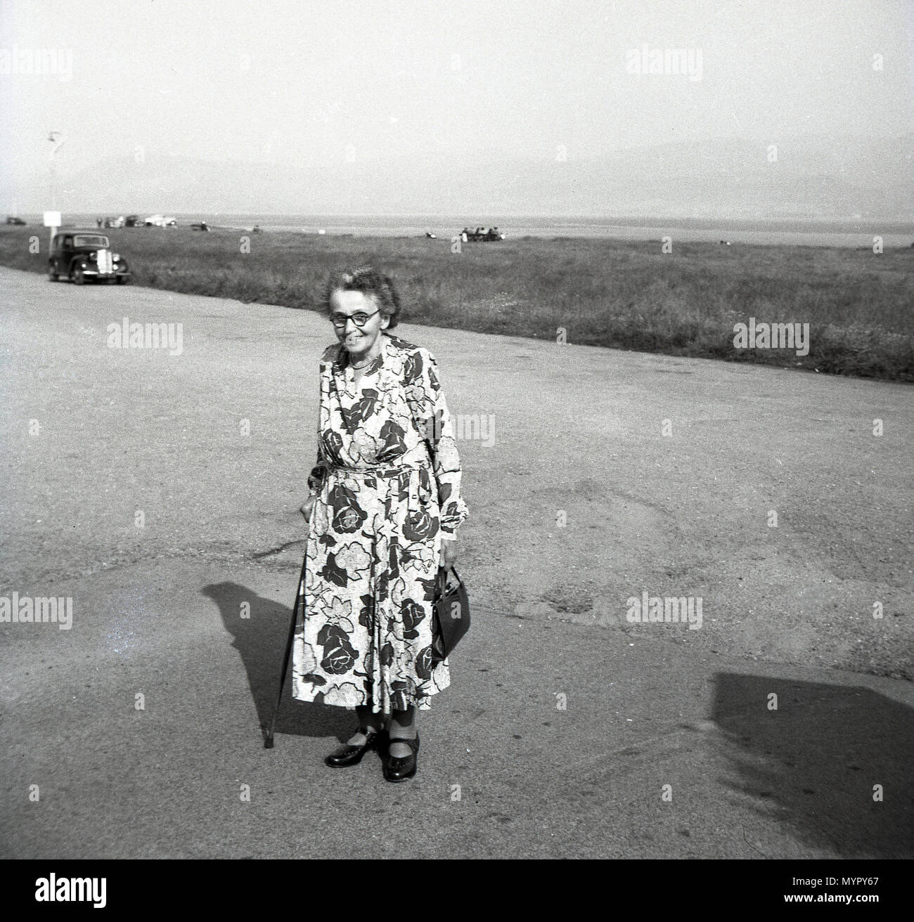 1953, July, England, historical picture of an elderly English lady with stick wearing a flowery dress standing outside on a road near the coast. - Stock Image