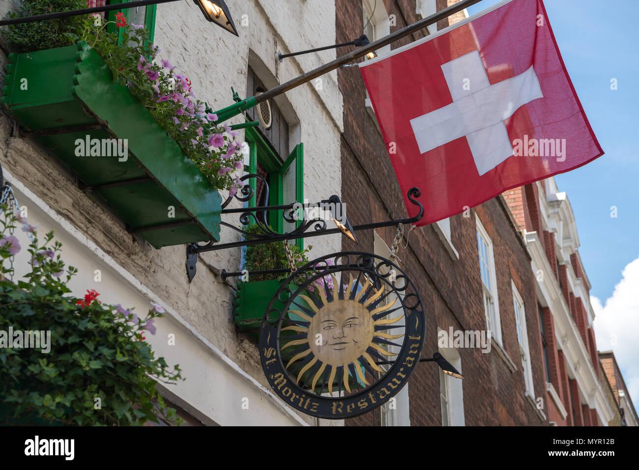 Sign and Swiss flag outside the St. Moritz restaurant, Wardour Street, Soho, London, England, UK - Stock Image