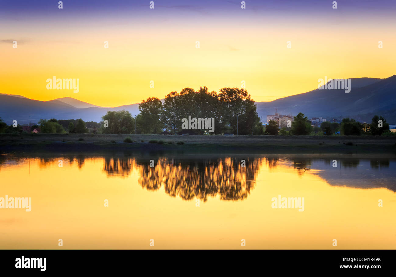 Perfect golden hour sunset over calm, reflective lake with gradient in the sky and silky, glowing water - Stock Image