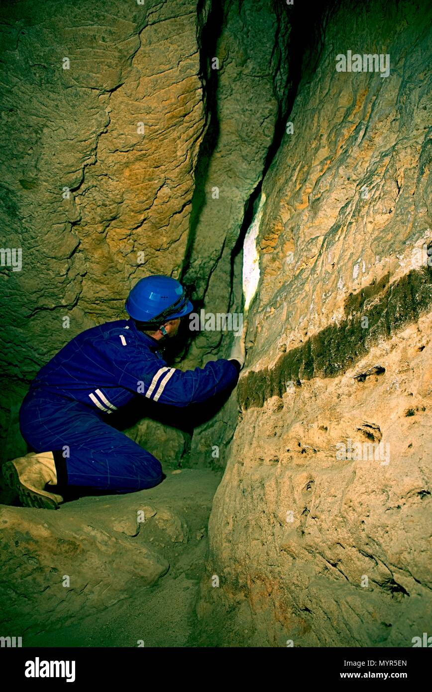 Workerman with helmet and protective suit using glowes and head lamp. Man do job in old mine ventilation shaft. Underground worker. - Stock Image