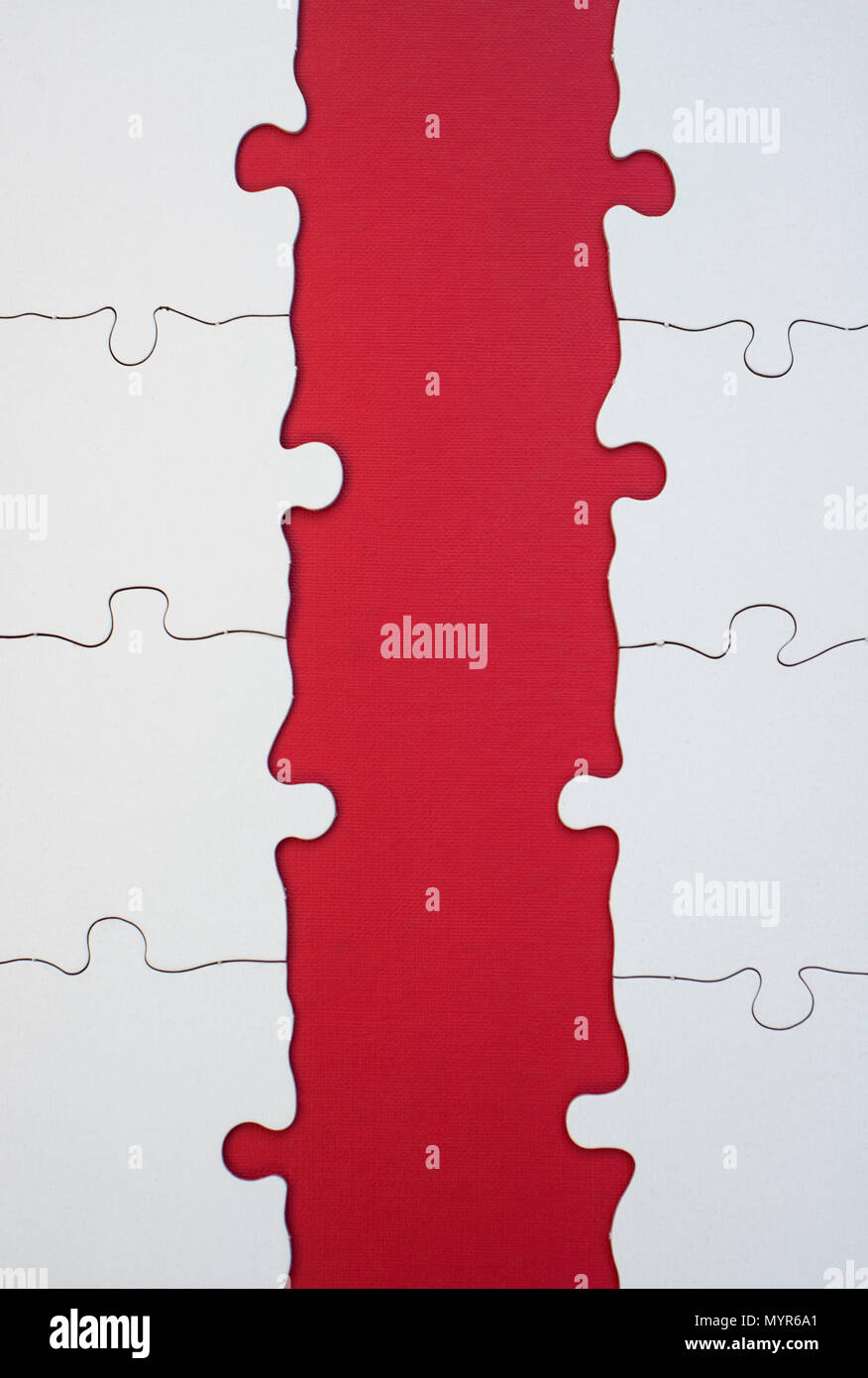 Detail of an incomplete all-white jigsaw puzzle on a red background - Stock Image