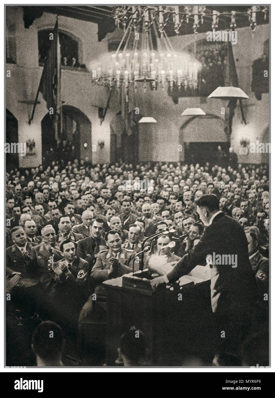 Vintage B&W image reportage Adolf Hitler giving a speech in Munich, with Goebbels wearing a swastika armband and Goering in the front row  November 1930 - Stock Image