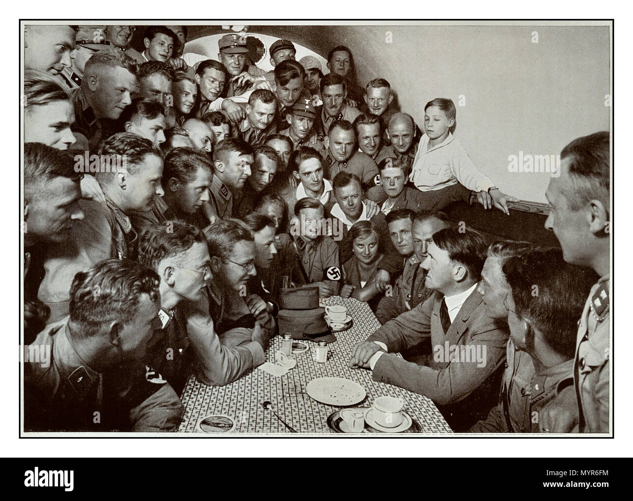 1930's Adolf Hitler speaks to a group of young messianic followers in the basement canteen of the Munich Brown House, a hostel for Nazi SA young men Munich Germany - Stock Image