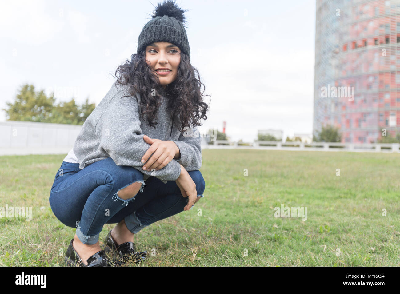 portrait of a woman with wool cap and sweater crouched on a grass garden - Stock Image