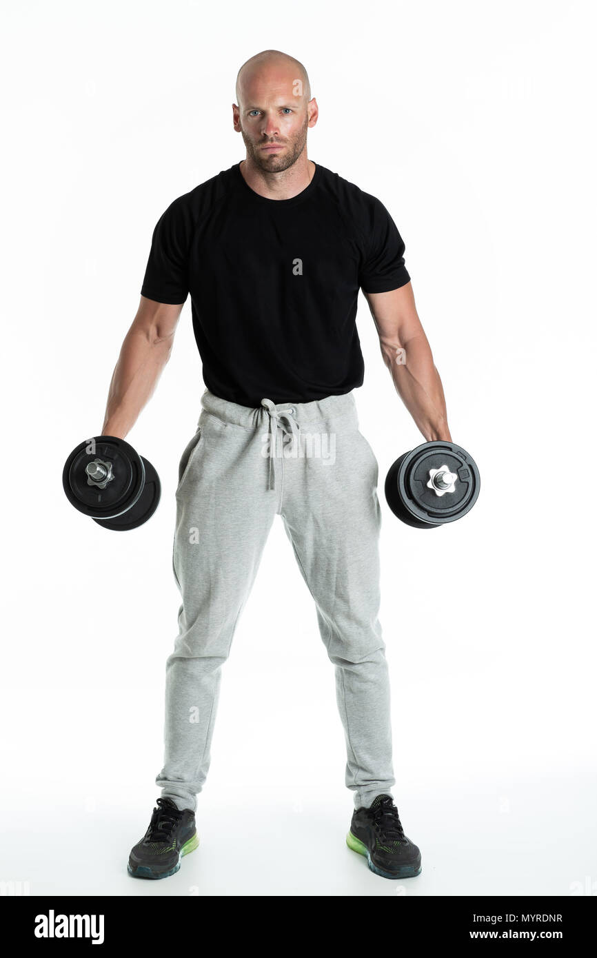 Athletic body builder pumping up muscles with dumbbells on white background - Stock Image