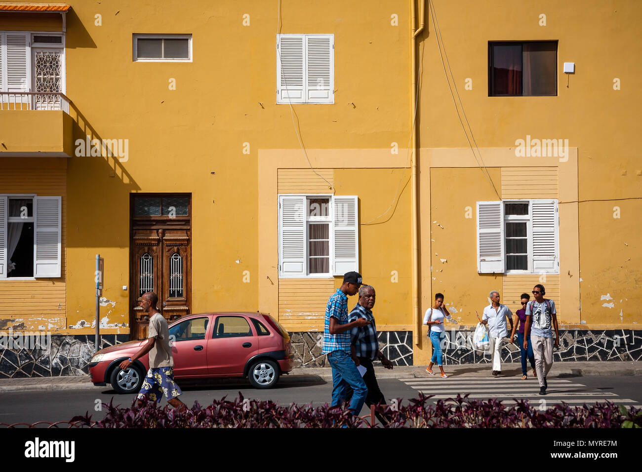 Life in Mindelo, residents walking the streets. Town architecture,  large yellow building wall MINDELO, CAPE VERDE - DECEMBER 07, 2015 Stock Photo