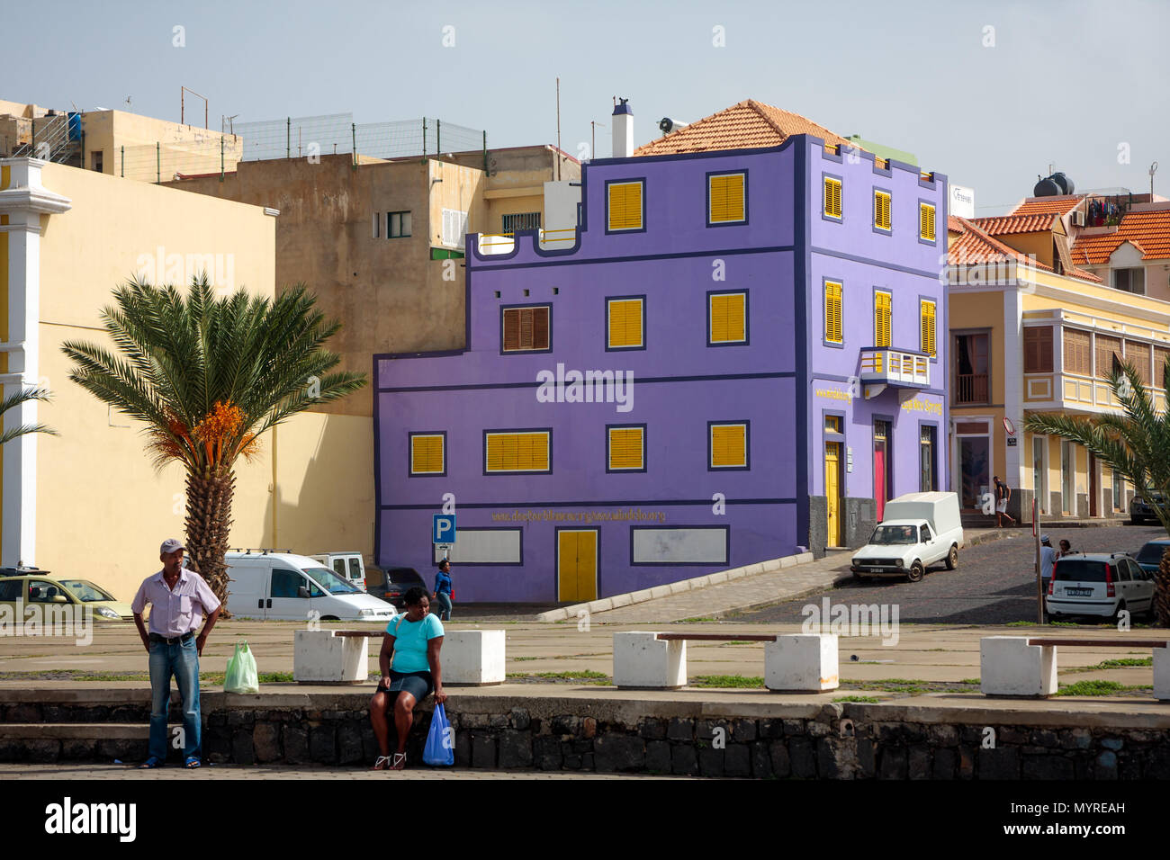 Vibrant violet building. Colorful architecture of Mindelo Town. People waiting for a transport MINDELO, CAPE VERDE - DECEMBER 07, 2015 Stock Photo