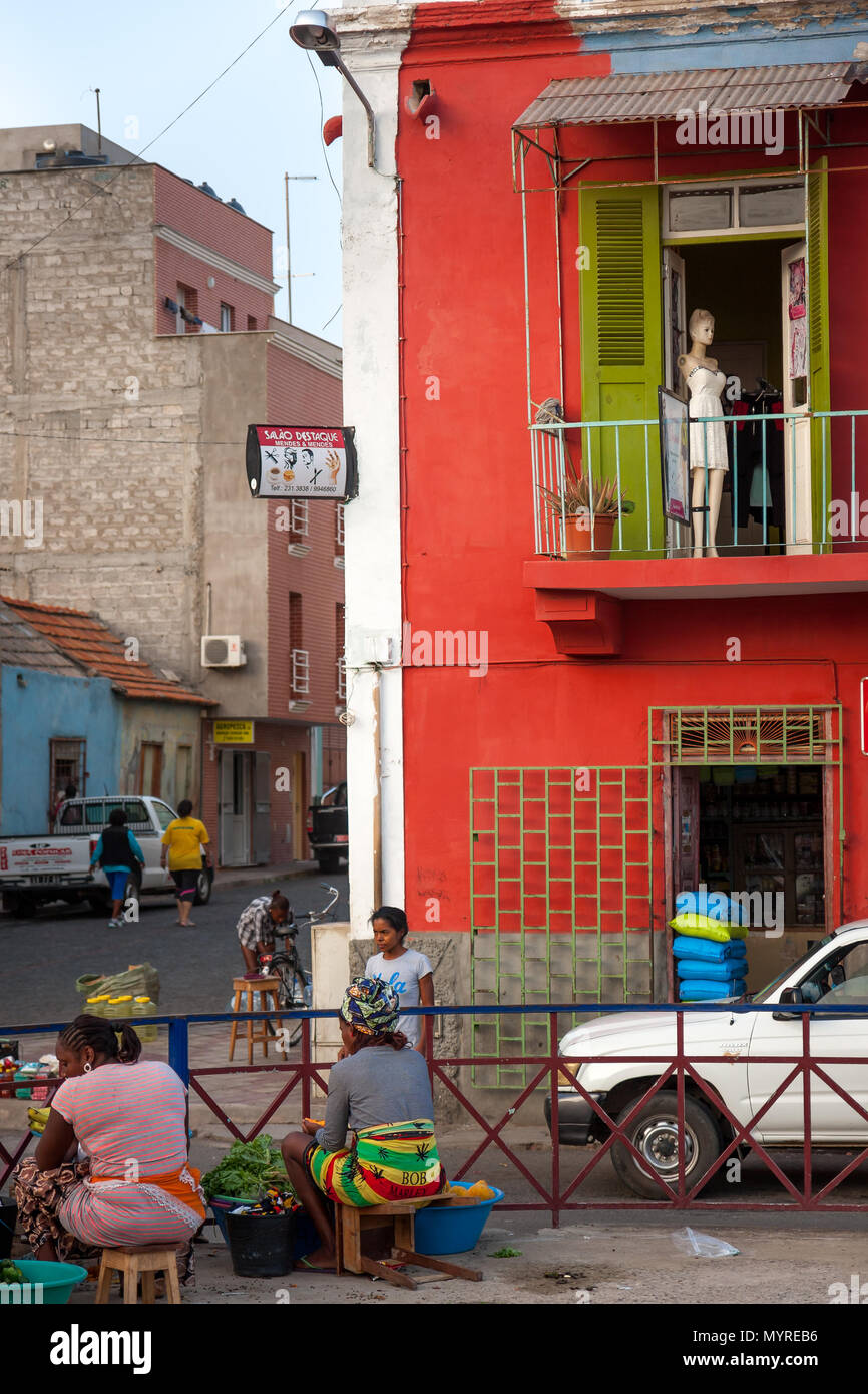 Life in Mindelo, residents selling goods at the square market fair. Red wall with a mannequin in the window MINDELO, CAPE VERDE - DECEMBER 07, 2015 Stock Photo