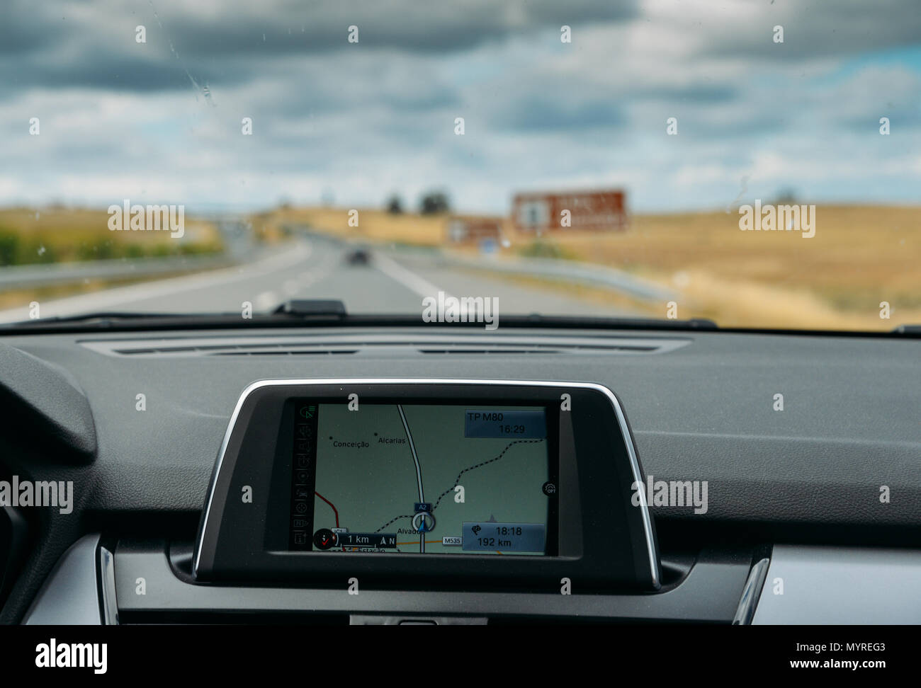 Selective focus of built in GPS navigator on dashboard of a car going down the scenic highway in Algarve, Portugal - Stock Image