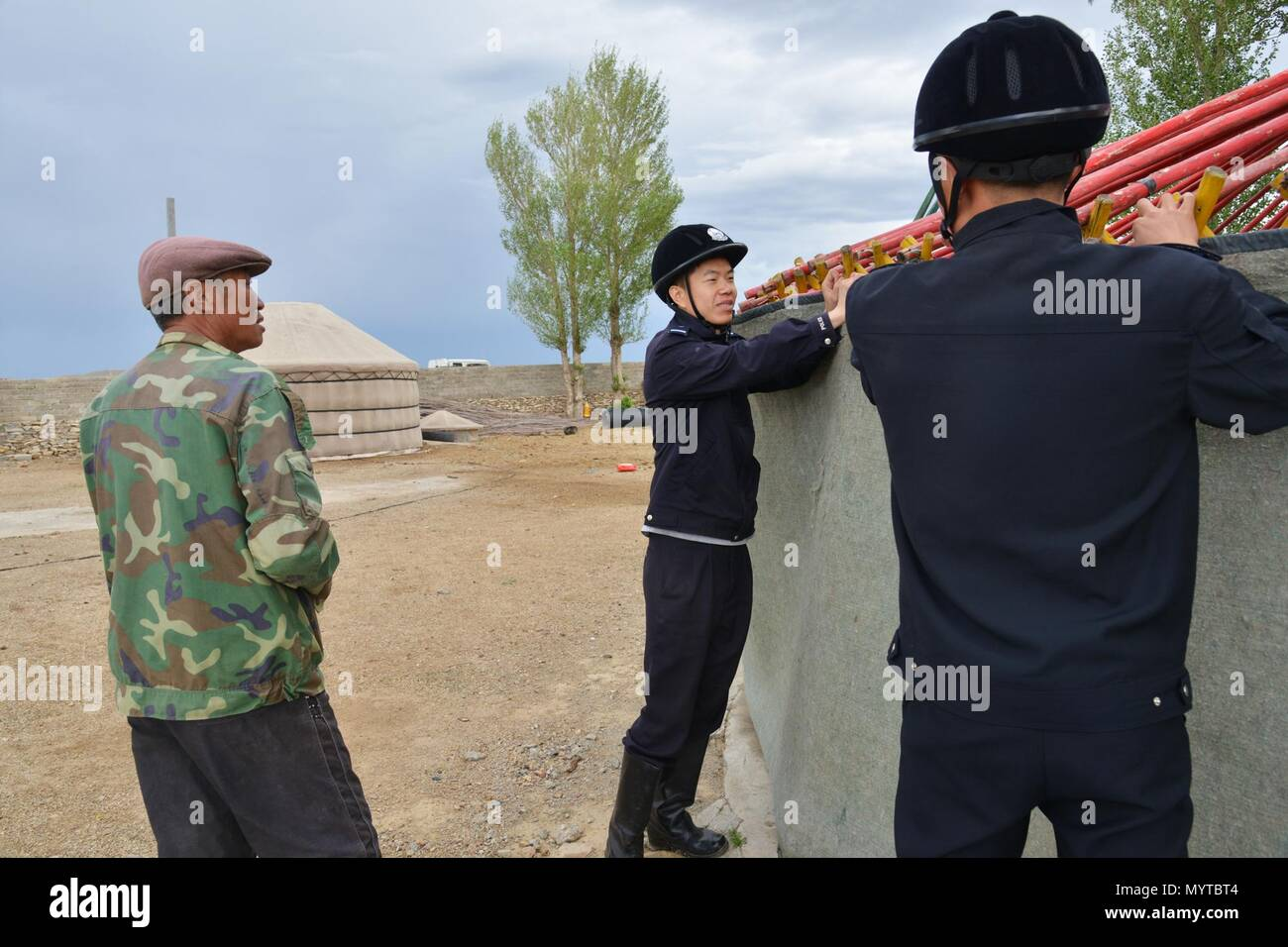 (180608) -- XILINHOT, June 8, 2018 (Xinhua) -- Mounted policemen help a herdsman build Mongolian yurt in Xilinhot, north China's Inner Mongolia Autonomous Region, June 7, 2018. In order to keep railroads in operation, mounted police in Xilinhot are busy repairing broken safety net and checking livestock intrusion while patrolling along railroads. (Xinhua/Zou Yu) (wyl) - Stock Image