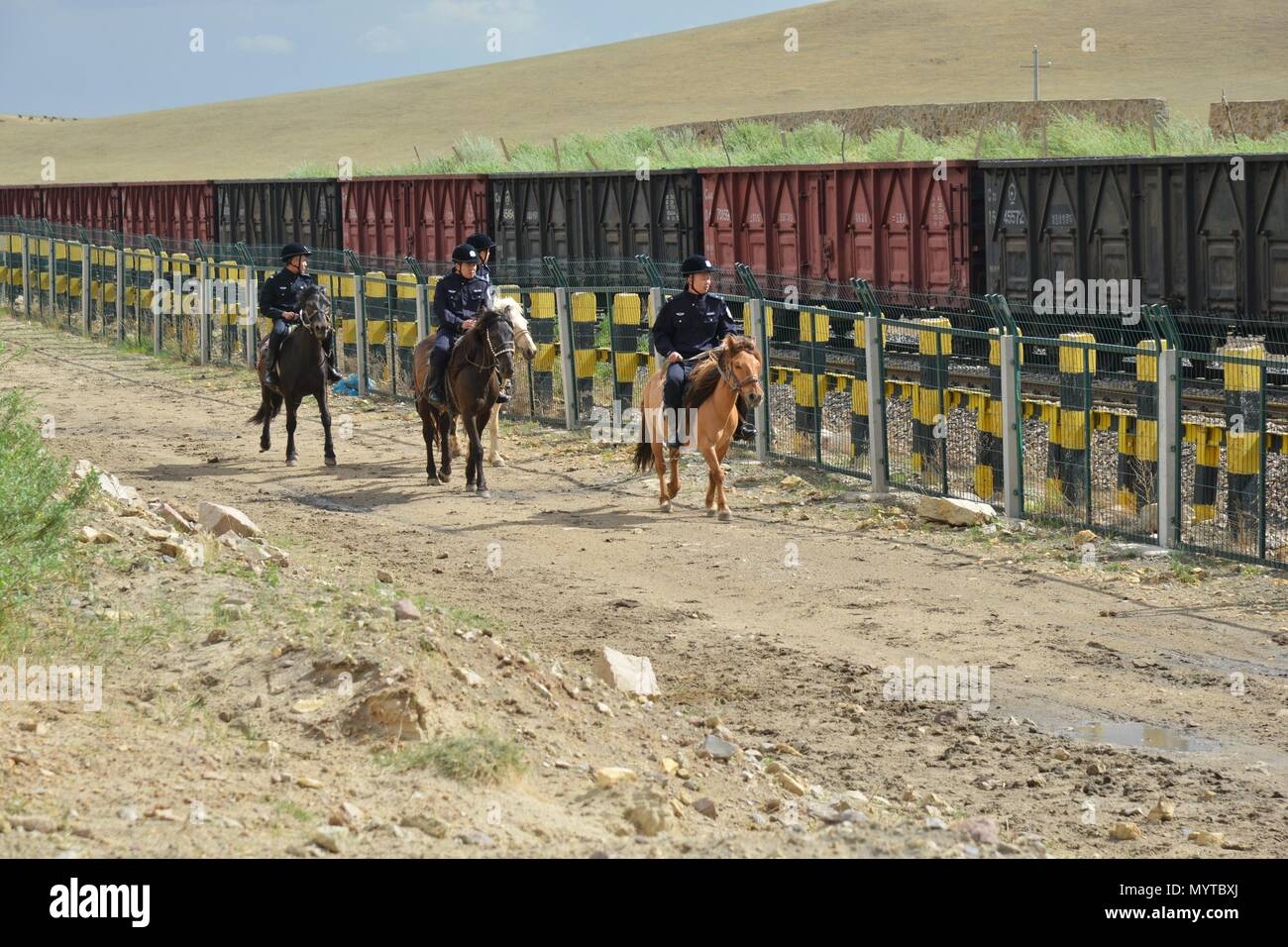 (180608) -- XILINHOT, June 8, 2018 (Xinhua) -- Mounted policemen patrol along railroad in Xilinhot, north China's Inner Mongolia Autonomous Region, June 7, 2018. In order to keep railroads in operation, mounted police in Xilinhot are busy repairing broken safety net and checking livestock intrusion while patrolling along railroads. (Xinhua/Zou Yu) (wyl) - Stock Image