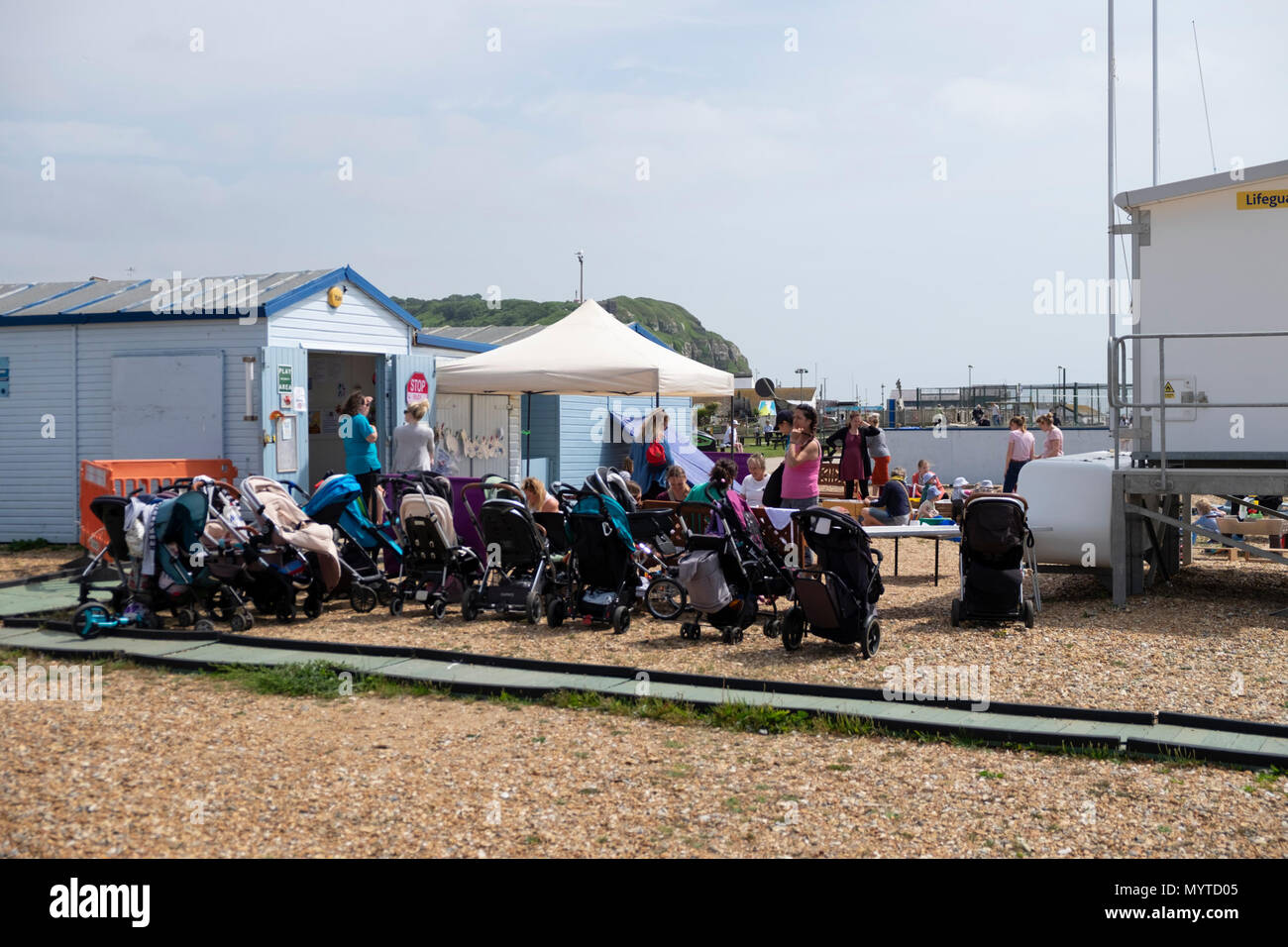 Hastings, East Sussex, UK. 8th Jun, 2018. UK Weather: Sunny but windy in Hastings this morning. This mum and baby group line up their pushchairs as they let the toddlers play on the sand. © Paul Lawrenson 2018, Photo Credit: Paul Lawrenson / Alamy Live News - Stock Image