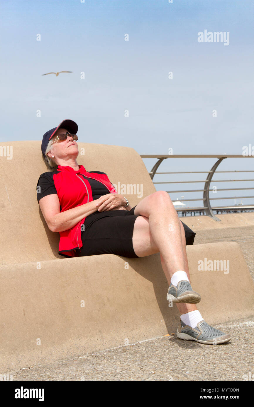 Blackpool, Lancashire, UK. 8th June, 2018. Sunny Day in Blackpool, Lancashire. UK Weather.  Carol Evans [MR] takes a well earned rest as she soaks up the fantastic sunshine beaming down on the famous Golden Mile on the seafront promenade at Blackpool in Lancashire.  Credit: Cernan Elias/Alamy Live News - Stock Image