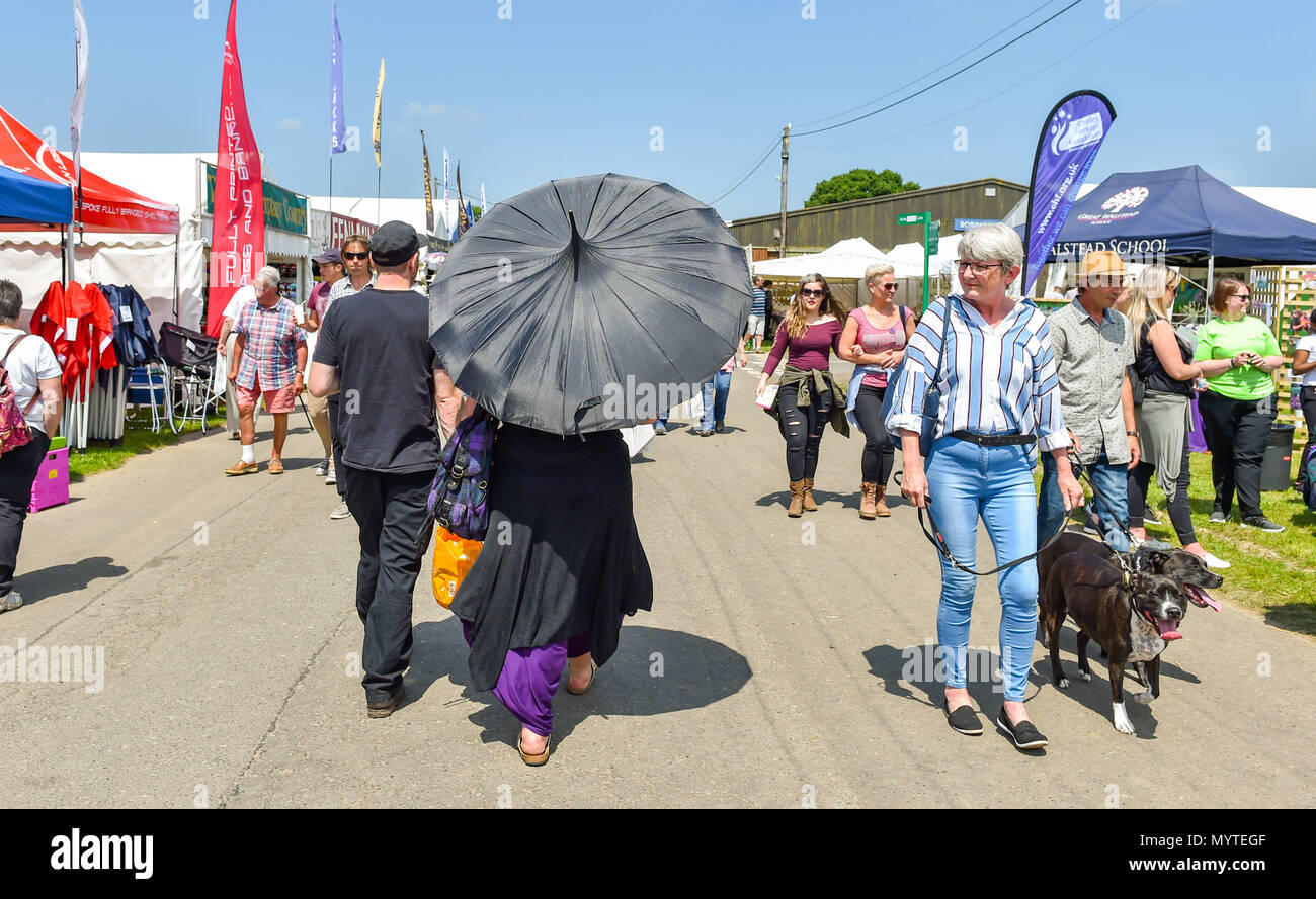 Ardingly Sussex UK 8th June 2018 - This lady stays in the shade under her parasol at the South of England Show in beautiful sunny weather held at the Ardingly Showground near Haywards Heath Sussex Photograph by Simon DackCredit: Simon Dack/Alamy Live News Stock Photo