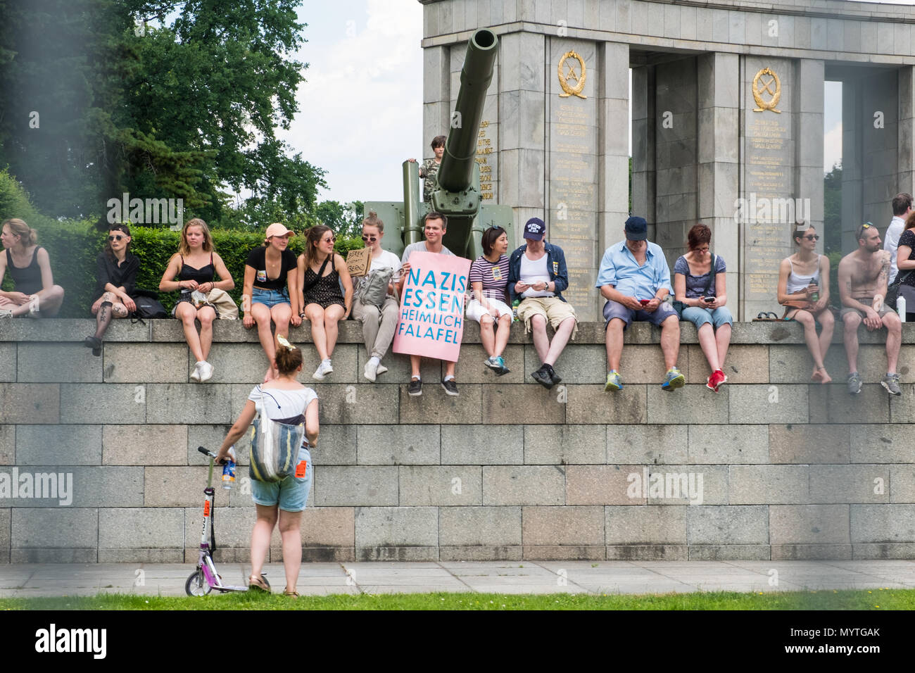 Berlin, Germany - march 2018: Group of Protesters sitting on wall in Berlin one holding sign with slogan 'Nazis secretly eat falafel ' (german: Nazis  - Stock Image