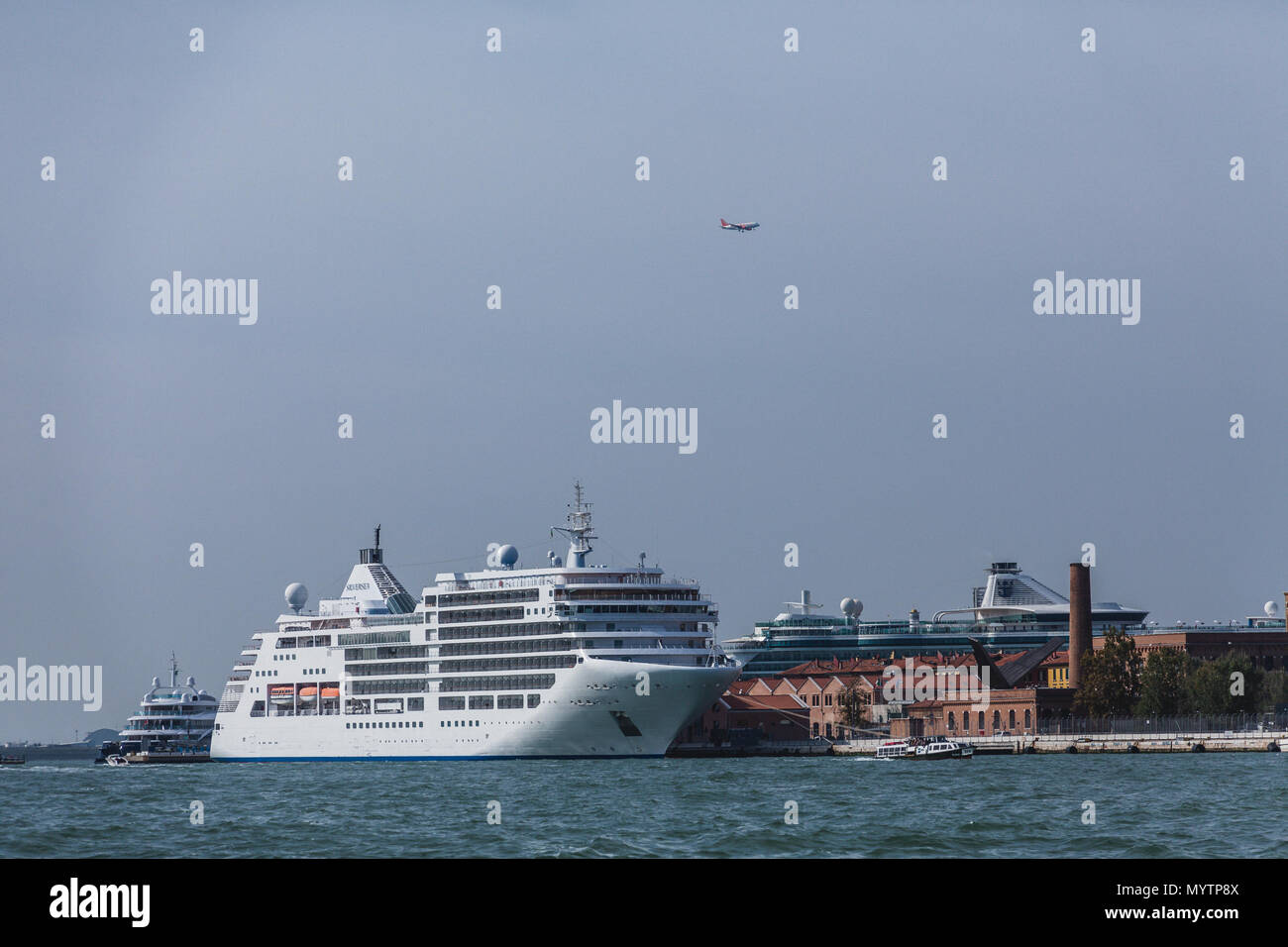 Airplane Over Cruise Ships in Venice Stock Photo