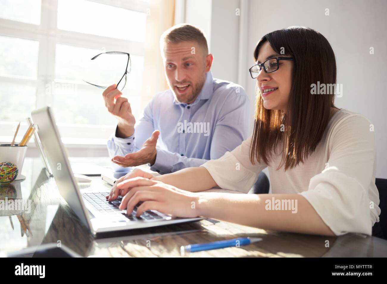 Angry man complaining to collegue at workplace in office - Stock Image