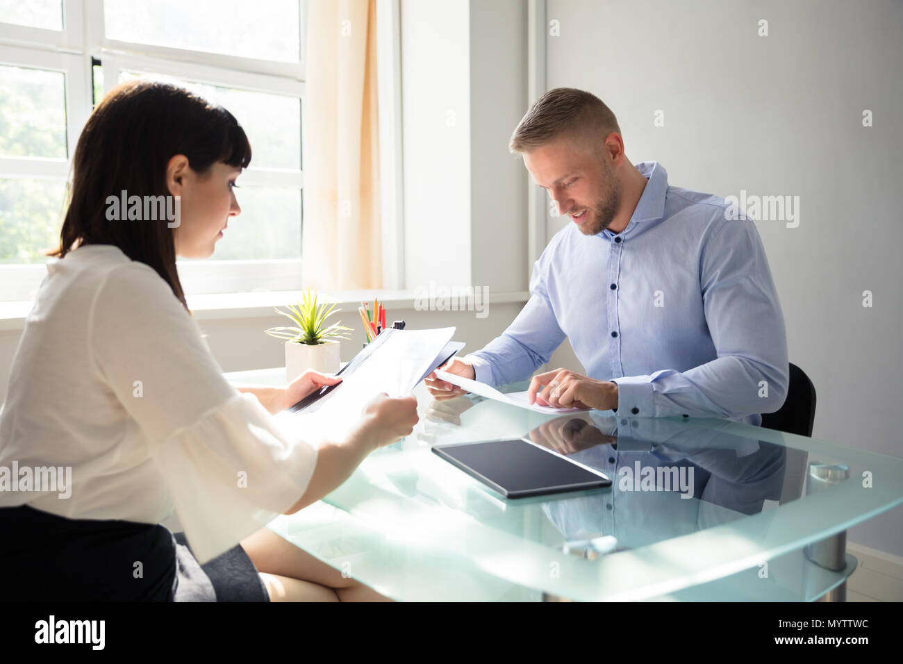 Two Young Businesspeople Looking At Document In Office - Stock Image