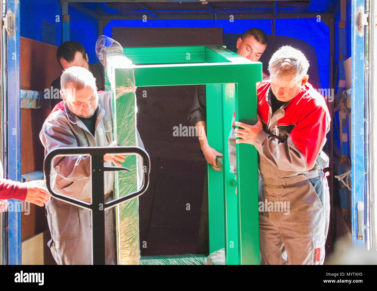 Men workers at factory production dragged the heavy object Stock Photo